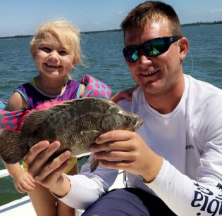 Hallie Kate and Captain Jared with a baby flounder